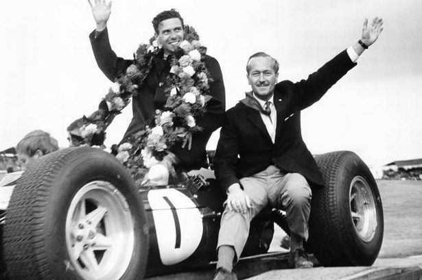 Colin-Chapman-former-chief-of-Lotus-Racing-celebrates-with-driver-Jim-Clark-after-his-win-in-the-1964-European-Grand-1863483